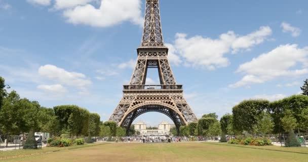 Eiffelova věž v Paříži a zelené louky na Marsu, lidé a turisté za slunečného letního dne, modrá obloha