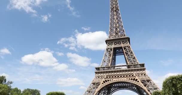 Eiffelova věž v Paříži za slunečného letního dne, modrá obloha s mraky ve Francii