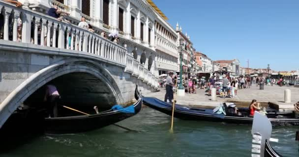 Lidé a turisté na gondole a procházky po mostě a docích v slunečném letním dni v Benátkách, Itálie