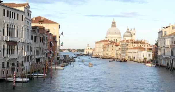 Grand Canal v Benátkách s bazilikou Svaté Marie zdraví, motorové čluny s lidmi a slunce v dopoledních hodinách v Itálii
