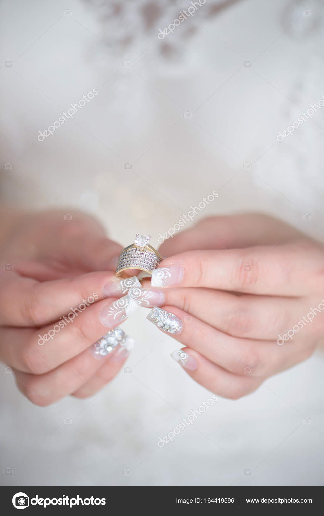 Vertical shot of young Caucasian bride holding a diamond wedding ...