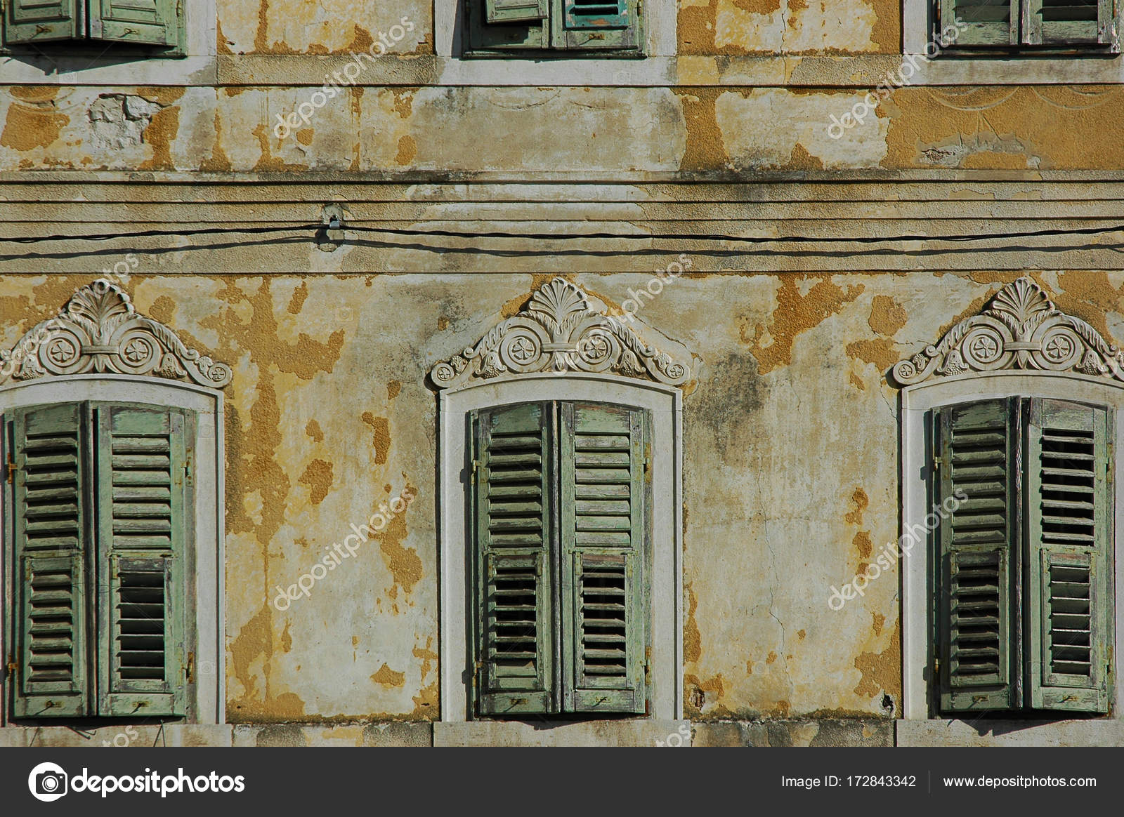 Weathered Window Shutters Of An Abandoned House With Ornate