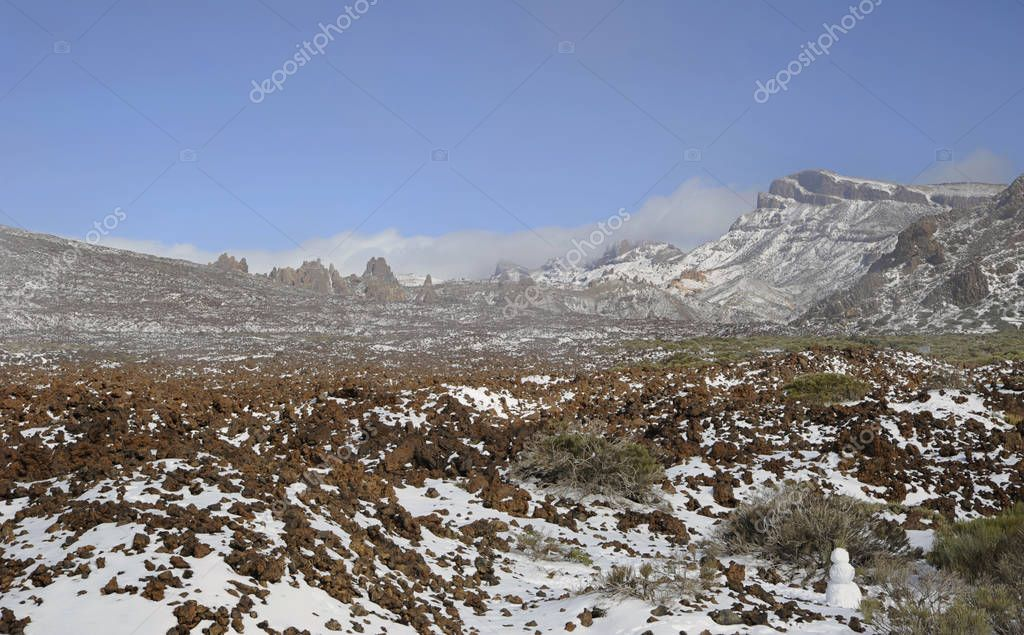 Clear day with thin, low clouds at horizon, vistas towards Llano de Ucanca, covered in snow, at the high altitude of Las Canadas del Teide, Teide National Park, Tenerife, Canary Islands, Spain