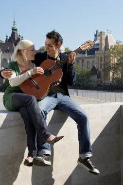 Couple playing guitar outdoors