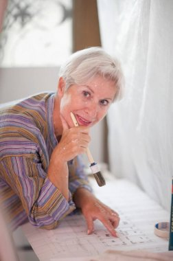 Mature caucasian woman with working plan and brush, looking at camera