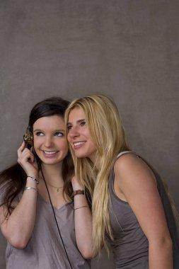 Teen girls listening music with headphones