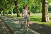 young attractive woman walking with bicycle at park