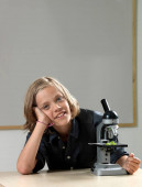 Boy with microscope looking at camera on classroom