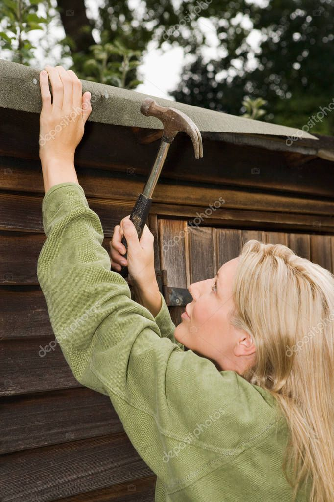 pretty caucasian young woman fixing her shed at garden