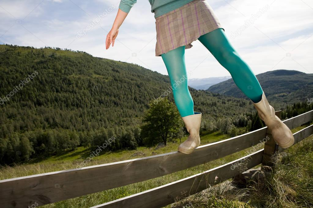 young woman walking on wooden fence