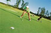 Muž hraje golf na hřišti