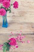 Zátiší s květinou růžová růže v modrou vázu na grunge dřevěné
