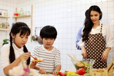 Asia two children and family are cooking food in the kitchen on a holiday.