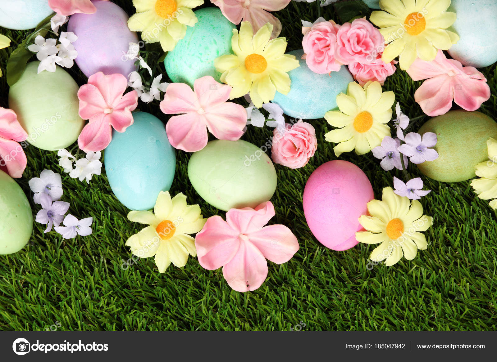 Colorful Easter Eggs On Grass With Flowers Background Stock Photo