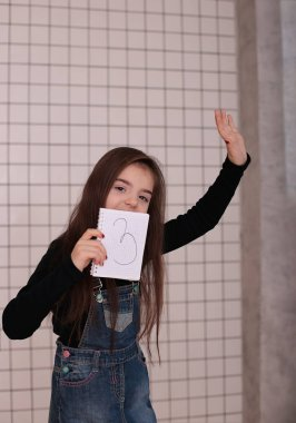 young smiling girl of eight years with long hair in a black turtleneck and denim sundress with the sign
