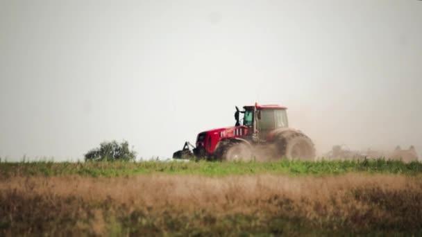 Zemědělský traktor připravuje prašnou půdu zasaženou suchem