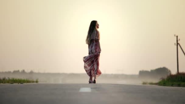 Mladá, hezká dívka kráčí v dlouhých šatech po cestě bosá v letním teplém večeru