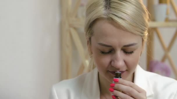 A beautiful, attractive woman sniffs a bottle of essential oil in an aromatherapy salon, a concept of beauty and health