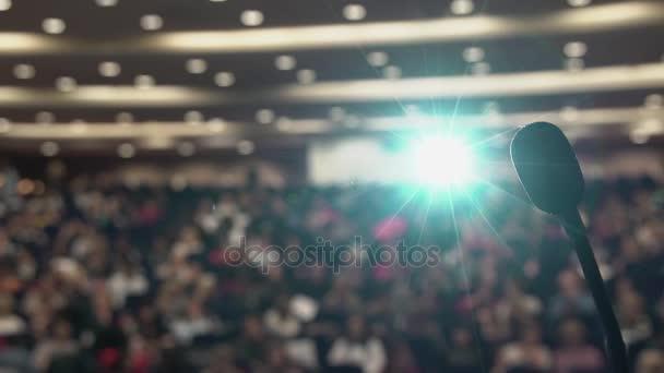 Mnoho lidí sedí na velkém sále na konferenci. Projektor světlo přes mikrofon