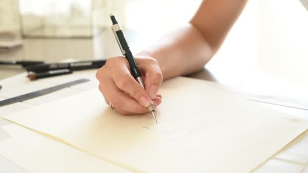 Designer writing logo. Designers hand holding a pen and writing logo. Woman designer at work in her office working on project