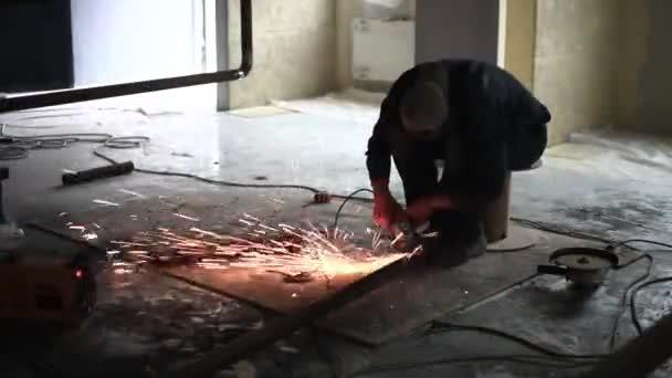 Člověk pracuje kotoučová pila. Mouchy jiskra z roztaveného kovu. Jeho tvrdé práce. Muž Chlef a hladký povrch. Muži, kteří pracují ocel.