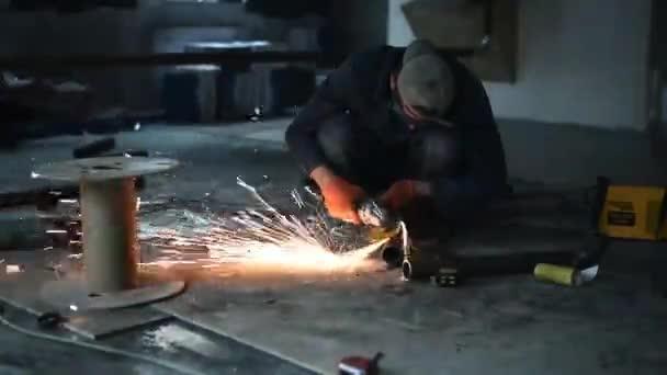 Svářeč v továrně. jiskry při broušení kovové úhlové brusky