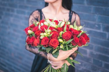 woman holding in hands bunch of red roses, crop