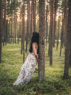 Lonely woman in dress standing and leaning on tree in green forest at sunset