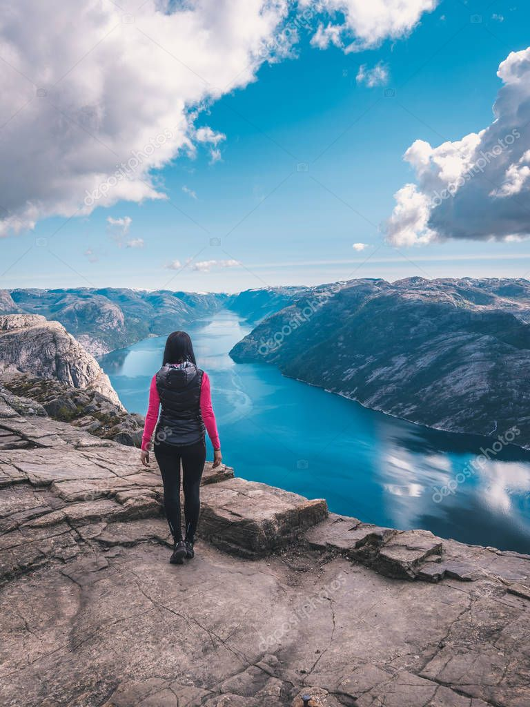 young woman standing on edge of beautiful rock in mountains of Norway.