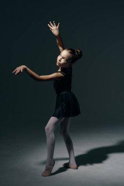 Beautiful girl ballerina dancing in light play and shadowson dark background