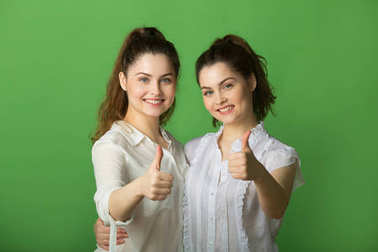 two beautiful positive girls with joyful emotions on a green background