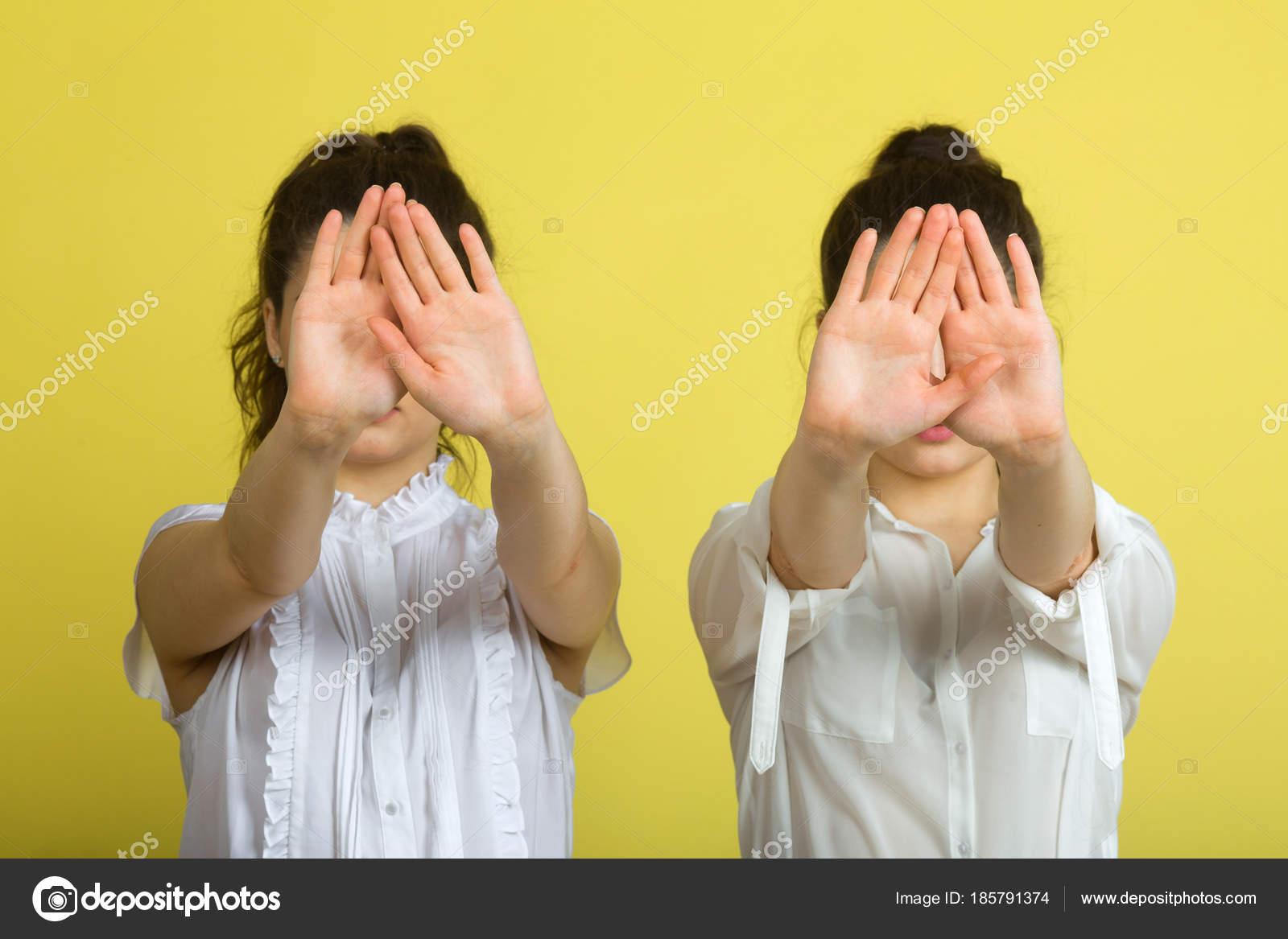 97581988d18f Δύο δίδυμα αδελφές όμορφη νεαρή κοπέλα σε λευκό μπλούζες σε κίτρινο φόντο  με σοβαρά αντιμετωπίζει και των κινήσεων των χεριών — Εικόνα από ...