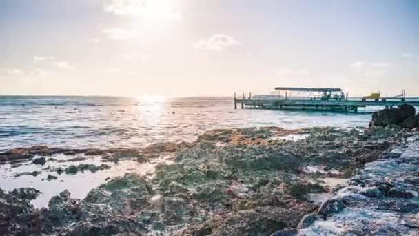 Moře v Bayahibe v Dominikánské republice zabrané v Time lapse, s molo, které působí jako hlavní předmět a slunce zapadá v pozadí
