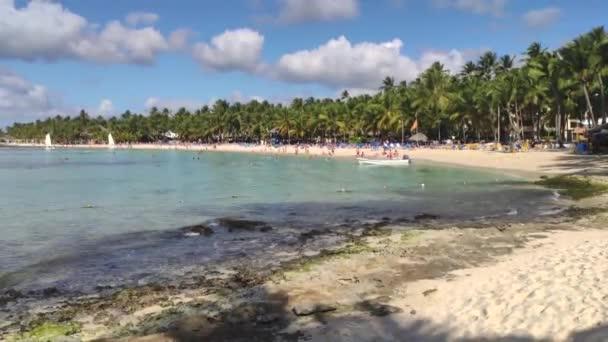 Kilátás Dominicus strand Bayahibe a Dominikai Köztársaság reggel a nap, a hajók a tenger és a pálmafák és a turisták lakott a strandon 2