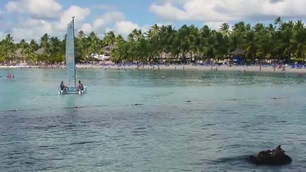 Kilátás Dominicus strand Bayahibe a Dominikai Köztársaság reggel a nap, a hajók a tenger és a pálmafák és a turisták lakott a strandon