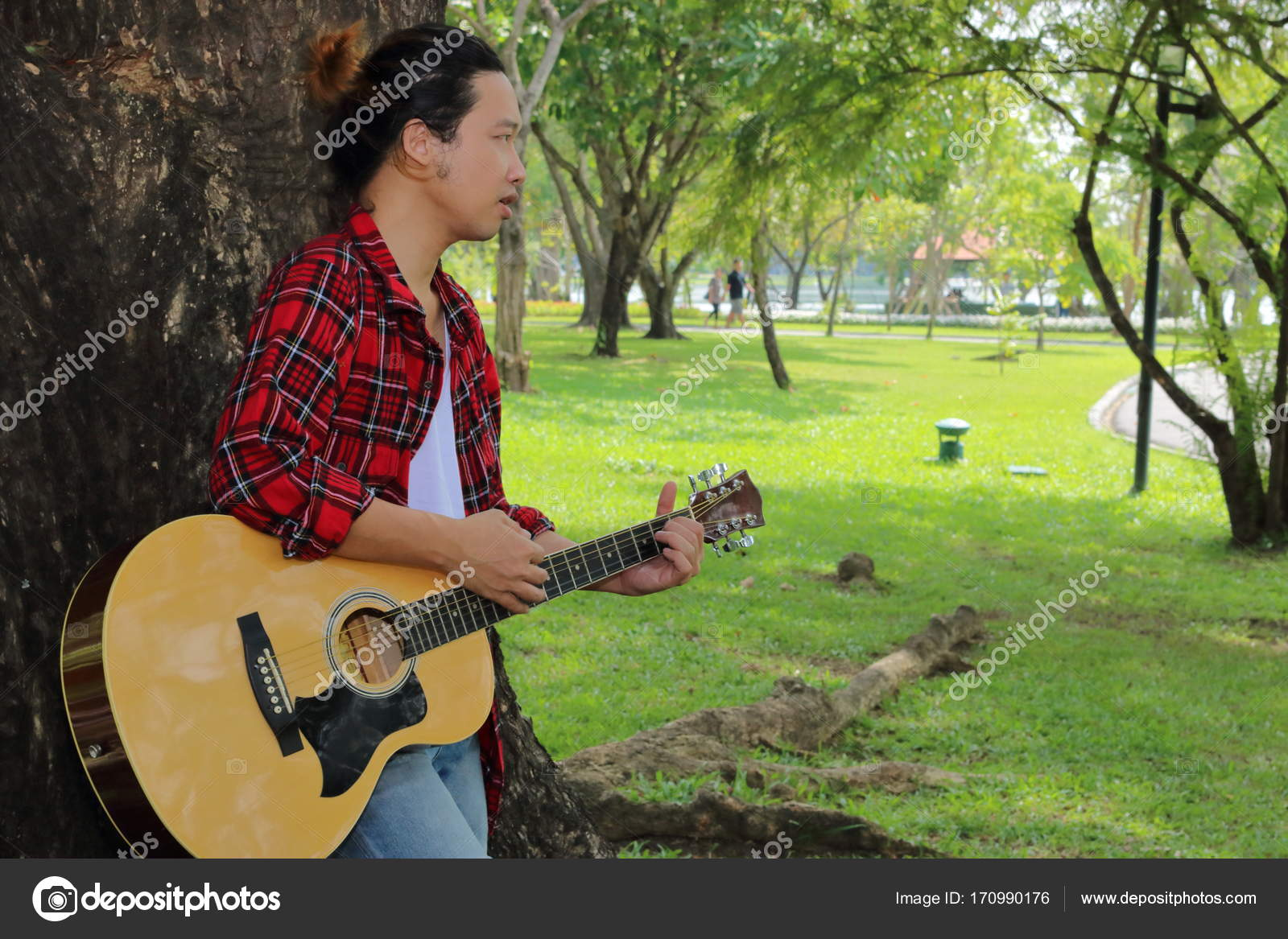 Portrait Of Young Guitarist Standing Against A Tree And Playing Acoustic Guitar In Beautiful Nature Background