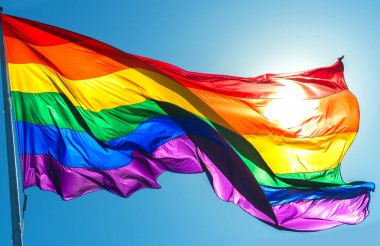 Rainbow flag on the blue sky background symbol of tolerance and