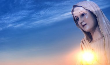 Statue of the Virgin Mary against sunrise