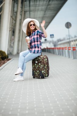 Tourist girl sitting on a suitcase with a disposable cup in her hand. Female traveler dressed in shirt plaid, hat and sunglasses waving hello someonewhile waiting for taxi near aorport terminal.
