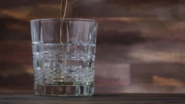 Arany whiskey-t vagy whiskyt öntenek üvegbe. A fa asztalon két pohár whisky vagy brandy. Alkoholos ital lassított felvételben
