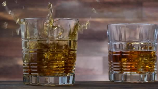 Ledová kostka padající do sklenice se zlatou whisky a alkoholem. Zpomalený pohyb