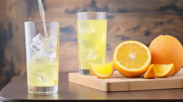 Narancsos szénsavas limonádét öntök üvegbe jégkockákkal. A fa háttér narancs gyümölcs. Vegetáriánus nyári ital