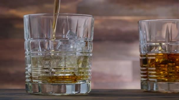 Arany whisky vagy scotch öntött üvegbe. A fa asztalon két pohár alkohollal lassított felvételen
