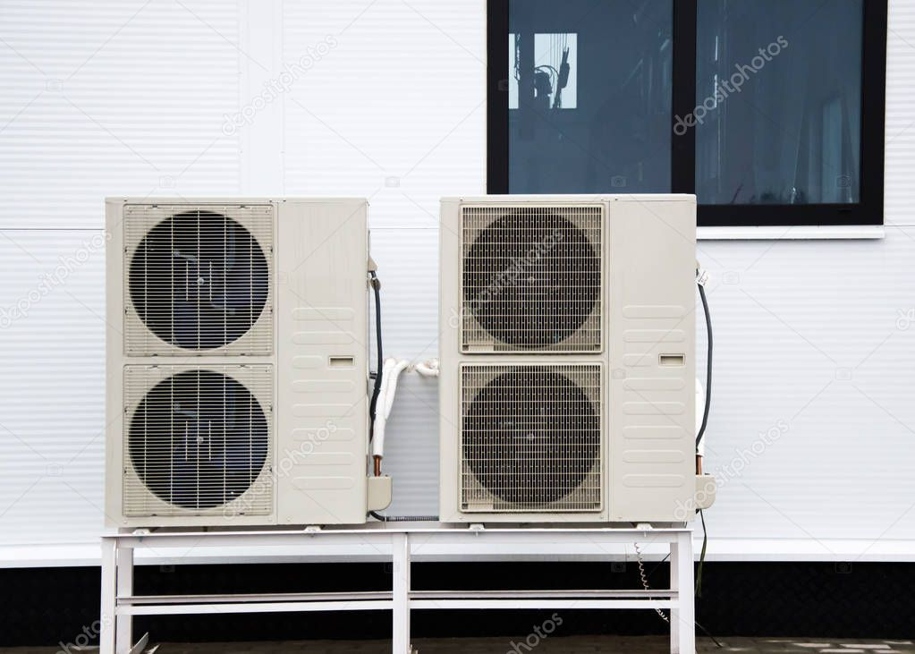 Two outdoor units of air conditioners standing on the ground in front of facade of the modern building