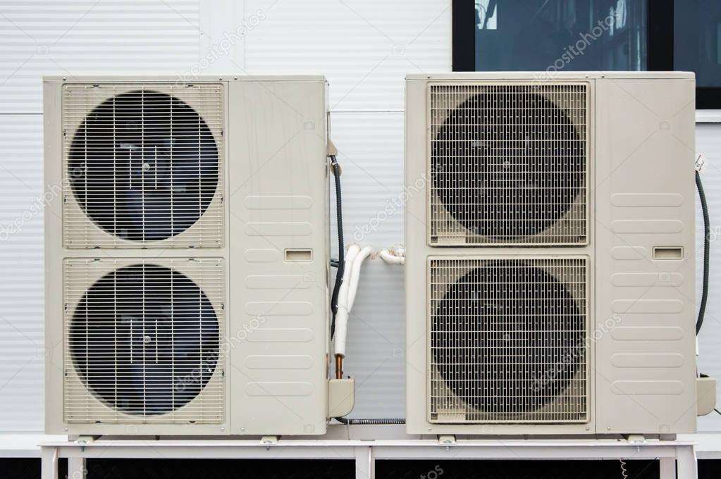Close-up photo of two outdoor units of air conditioners standing on the ground in front of facade of the modern building