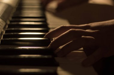 Close-up soft focused atmospheric photo of a hand playing the piano keys. Concept: Music creating, composing, lyrics, performance