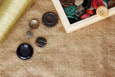 buttons and spool of thread on burlap