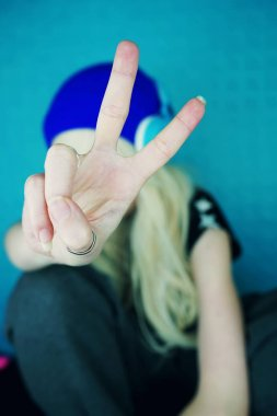 Portrait of young blonde woman in blue headphones listening to music on blue background and gesturing
