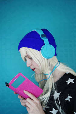 Portrait of young blonde woman in blue headphones listening to music and using phone on blue background