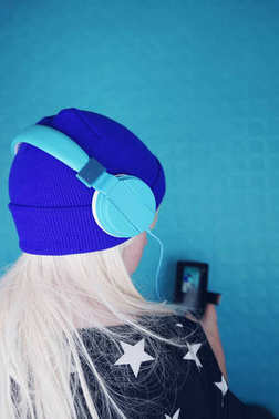 Portrait of young blonde woman in blue headphones listening to music on background